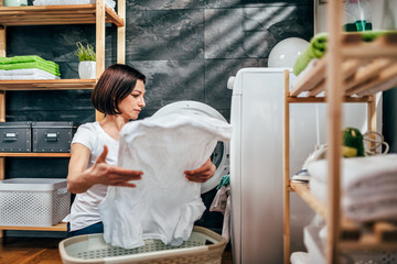 Woman taking clothes out washing dryer machine