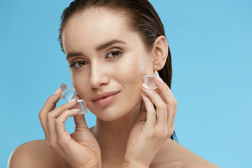 Face Skin Care. Woman Applying Ice Cubes