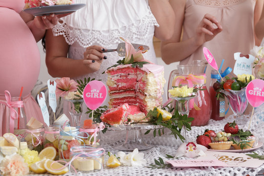 Group of women at a baby shower enjoying food and drink. Pregnant woman celebrating baby shower with female friends at home.