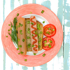 Simple breakfast. Sausage sandwich snack and vegetables on whole grain bread sprinkled with chopped onions. In white with a red dish. On a wooden blue background.