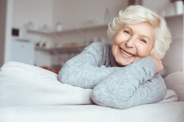 Portrait of handsome grandmother in gray sweater sitting sofa, relaxing Wall mural