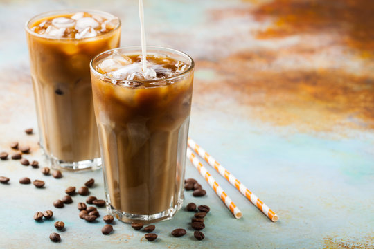 Ice coffee in a tall glass with cream poured over and coffee beans. Cold summer drink on a blue rusty background with copy space