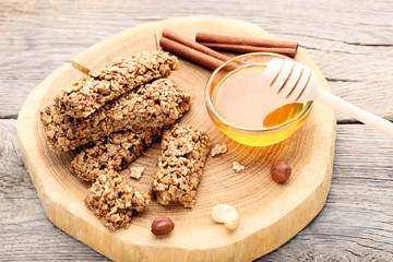 Tasty granola bars with honey in bowl and cinnamon on wooden table