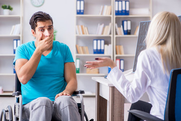 Disabled man in wheel chair visiting woman doctor