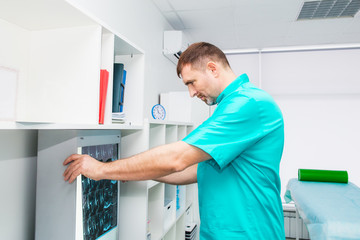 Male doctor looking at x-ray image of cervical spine in his office. Osteopathy, chiropractic, physiotherapy. Healthcare, roentgen, people and medicine concept. Selective focus, space for text.