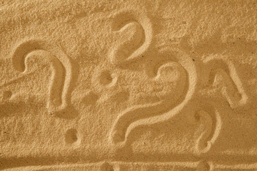 Question What and question mark symbols handwritten in sand beach