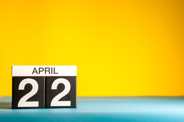 April 22nd. Day 22 of april month, calendar on table with yellow background. Spring time, empty space for text