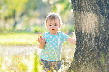 Little girl standing beside a big old tree. Happy child playing in beautiful summer park on warm sunny day.