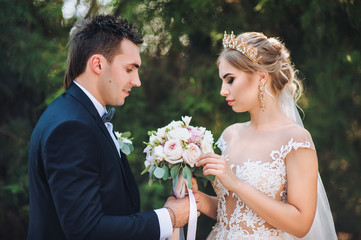 The bride gives her bride a wedding bouquet. A young beautiful bride in a lace dress is standing with the groom in the park. Wedding.