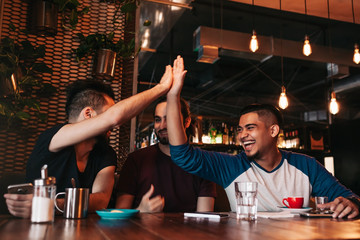Happy arabic young man giving high five to his friend. Group of mixed race people having fun in lounge bar