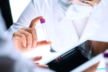 Closeup of scientific research team with clear solution in laboratory. Blonde female chemist holds test tube of glass while her colleague checks results with tablet pc. Blood test, medicine or