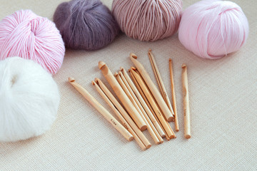 Wooden crochet hooks with balls of yarn pastel colors. Hoppy concept.