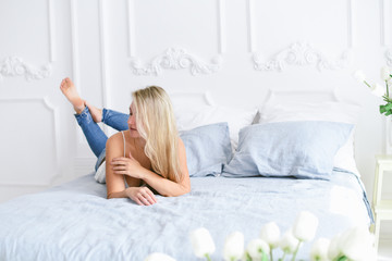Attractive girl on the bed in a blue interior bedroom with white tulips