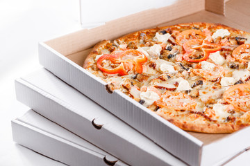 Pizza box delivery concept. Open box with hot tasty italian sliced pizza with salmon, eel, seafood, olives, basil, tomato, mushrooms.
