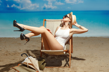 A girl on the beach sunbathing in a chaise lounger.