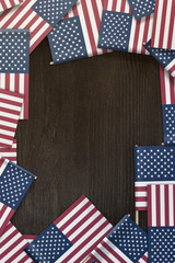 small American flags framing a wood texture background with copy space