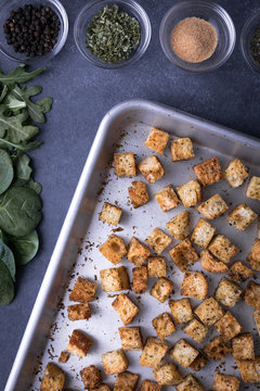 Flay lay of croutons on a baking sheet, with row of ingredients