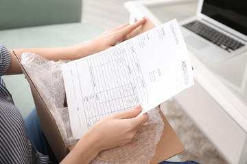 Young woman with purchase order sheet for parcel at home