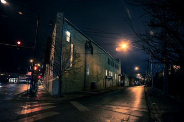 Fotomurales - Dark city street corner and alley with an industrial building at night