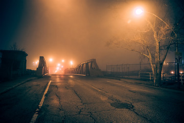 Wall Mural - Dramatic industrial vintage river road bridge street scene at night with illuminating fog in Chicago