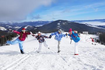 Happy friends on ski piste at snowy resort. Winter vacation