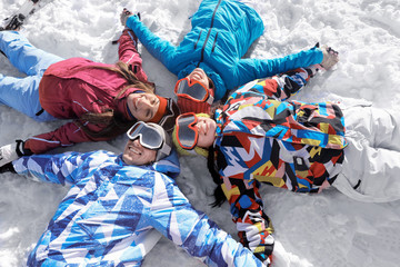 Friends lying on ski piste at snowy resort. Winter vacation