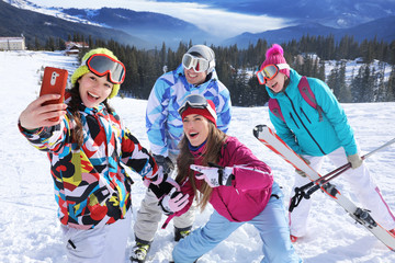 Happy friends taking selfie on ski piste at snowy resort. Winter vacation