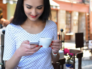Attractive woman in a street cafe with a phone. A girl at a lunch break drinks coffee and communicates through the messenger with her smartphone. The Internet. Message.