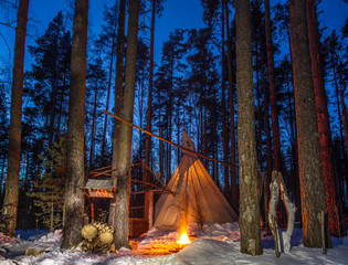 The wigwam stands in a snow-covered forest. The home of the Indians of Wigwam. Tipi with a burning caste. Night forest. Typical dwelling of nomadic people.