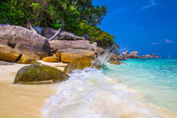 The turquoise wave is broken against the rocks. Rest in the tropics. Similan Islands. Beach holiday in Thailand. Travel around Phuket. Beach in Thailand. Boat trips.