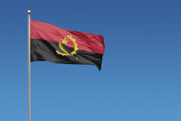 Angola flag in front of a clear blue sky