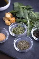 Glass ingredient dishes of dried thyme and spices