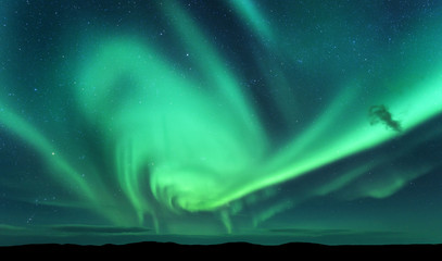 Aurora borealis and silhouette of hill. Lofoten islands, Norway. Aurora. Green northern lights. Sky with stars and polar lights. Night landscape with aurora, blue sky. Nature background. Concept