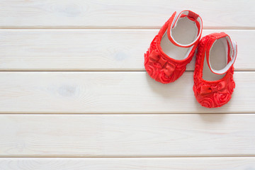 Children's shoes for a newborn girl. Red. Background light white wood.