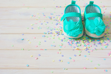 Children's shoes for a newborn girl. Turquoise. Background light white wood.