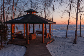 silhouettes of the pavilion and bird feeders against the backdrop of the sun setting in the winter lake