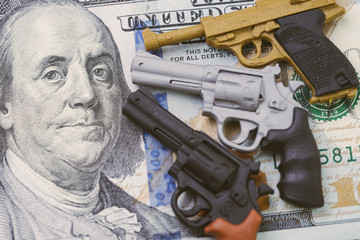 Big money in gun industry, gun control policy in united state of america after many of mass shooting, 3 miniature toy guns poiniting to face of US dallar banknote