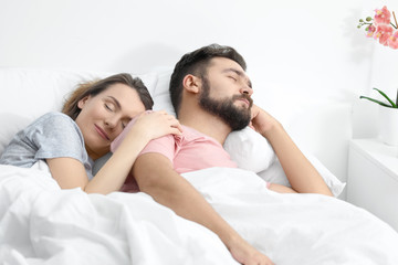 Husband and wife sleeping in bed at home