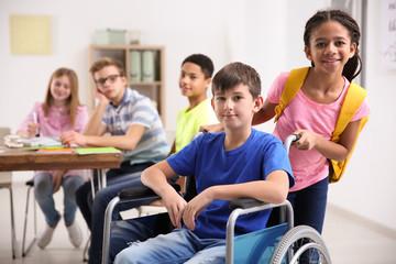 African American girl helping boy in wheelchair at school