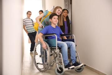Girl helping boy in wheelchair at school corridor