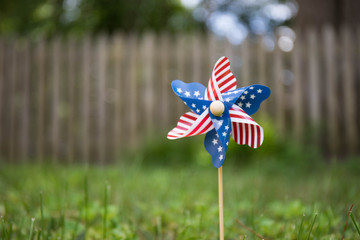 A close up bokeh photo of a pinwheel with the american flag stars and strips pattern.