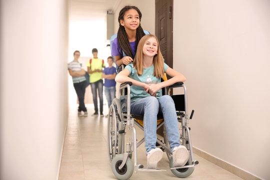 Classmate helping girl in wheelchair at school corridor