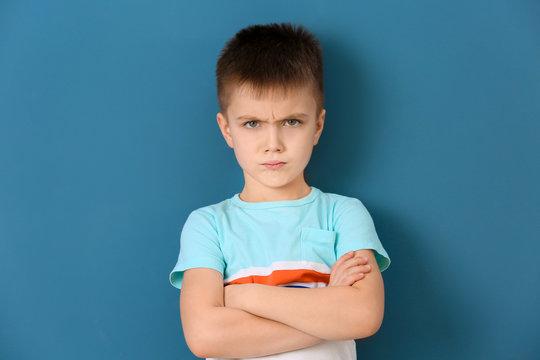 Portrait of emotional little boy on color background