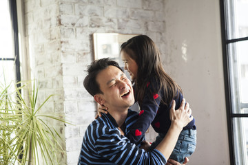 娘を抱きかかえるお父さん。