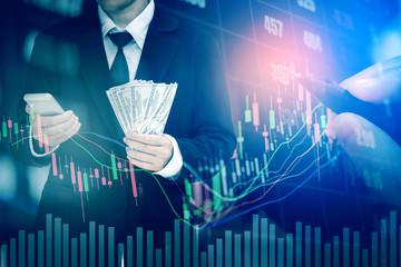 Businessman Holding money US dollar bills on digital stock market financial exchange information and Trading graph background