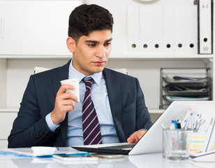 Adult man is working at a computer and drinking coffee