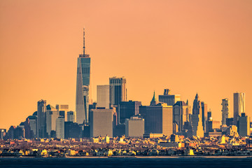 New York highrise skyline with lowrise Brooklyn borough in the foreground, as viewed at sunrise, from Sandy Hook, NJ.