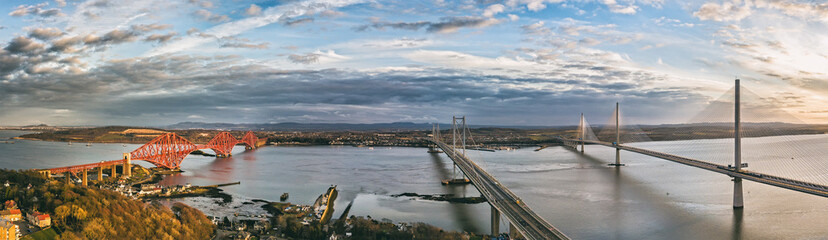 The new Queensferry Crossing bridge (on the right) over the Firth of Forth with the older Forth Road bridge (on the left) and with the iconic Forth Rail Bridge in the far left.