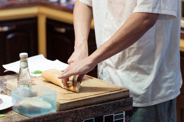 Cutting bread by knife in the kitchen