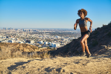 fit african american woman running at runyon canyon with los angeles in background